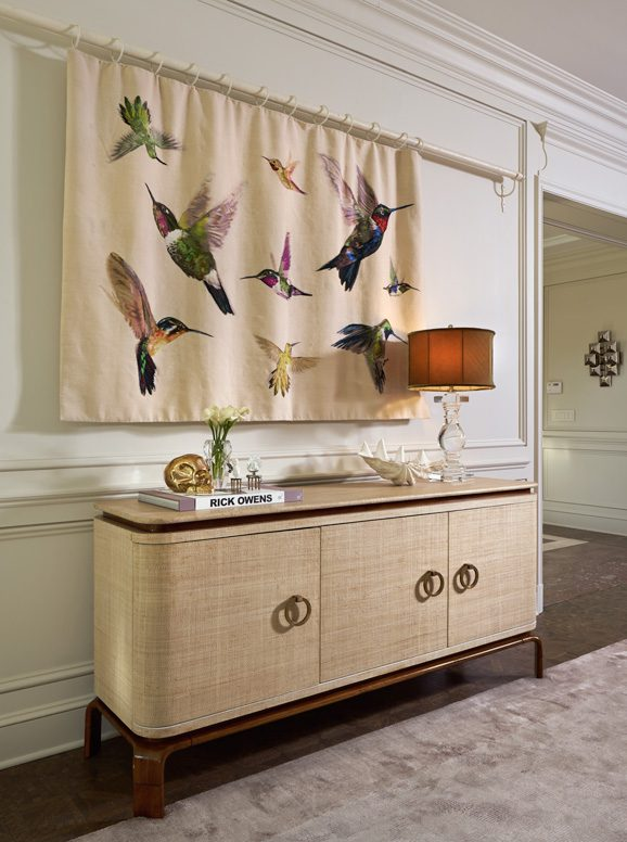 A hummingbird tapestry from the Alexander McQueen collection for The Rug Company hides a recessed flat screen television. Photo by David Cobb
