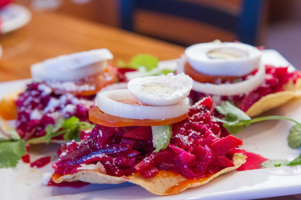 Guatemalan Enchiladas are topped with a choice of meat, pickled beets and other garnishes. Photo by Brent Fuchs.