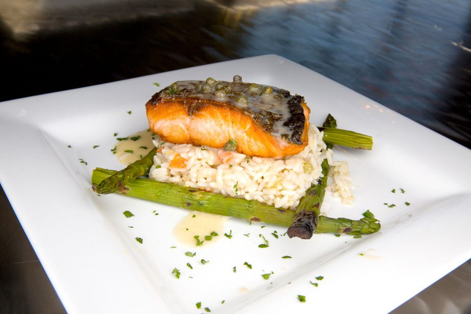 Pan Saumon Poele features pan-seared salmon over rice pilaf served with lemon caper buerre blanc and asparagus. Photos by Brandon Scott.