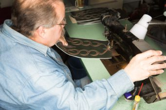 Smith sews vamps, counters, stitch work and pull straps onto each pair of custom-made boots with sewing machines original to the company.