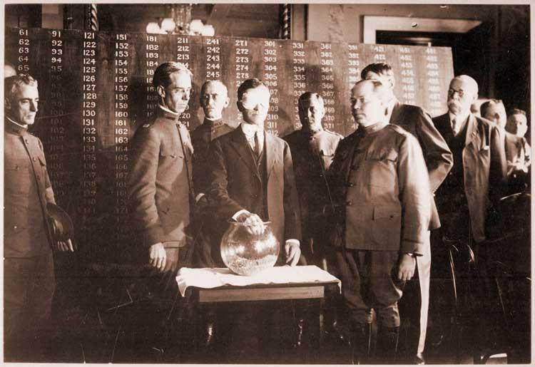 Secretary of War Newton Baker draws the first number of the lottery created by the 1917 Selective Draft Act.