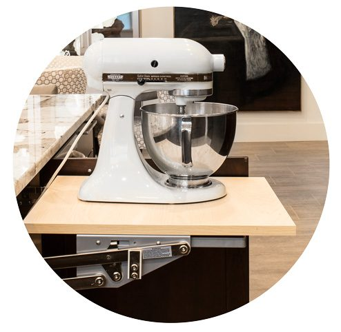 The homeowner requested  that the kitchen design offer ways to hide smaller countertop appliances. To accommodate this, Thorp installed cabinets and pop-up shelves beneath the counter and island to house these appliances, such as an espresso machine and a stand mixer.