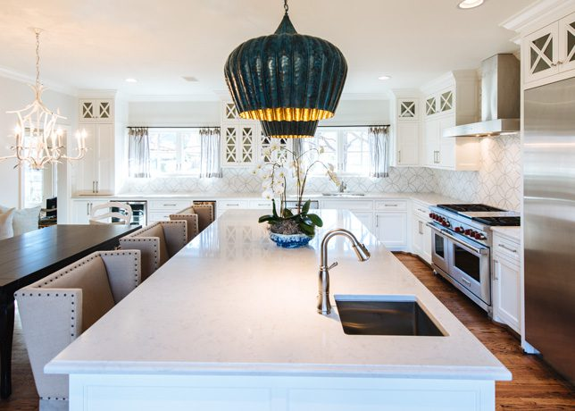 "The kitchen's upper cabinets faced in glass have recessed lighting, which displays the homeowner's china collection. Matching pendant lights that hang over the island provide that extra ""Ah ha!"", says Welch. Caesarstone quartz counters contribute to the open, airy feel of the room."