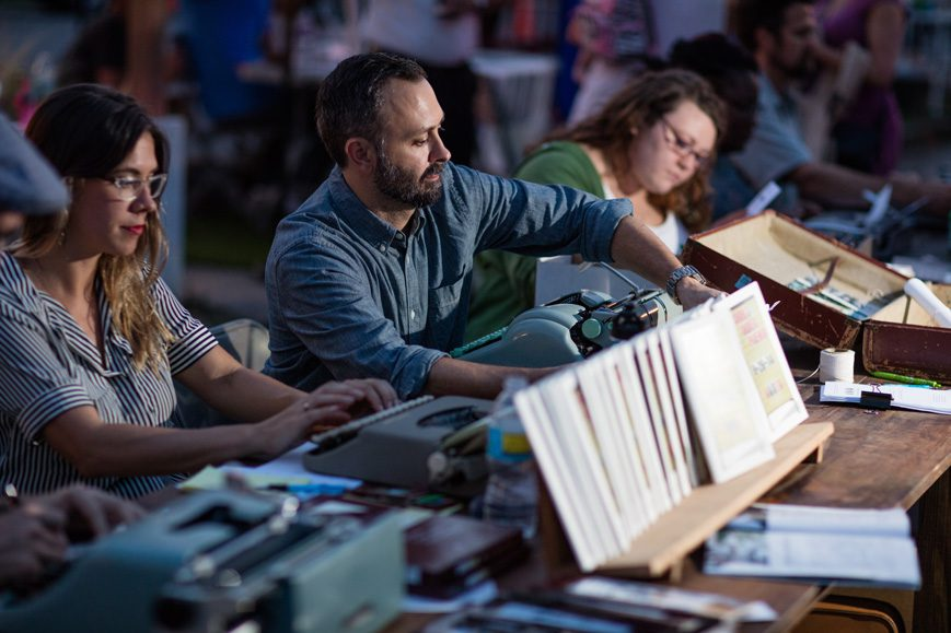 Chad Reynolds (center) writes made-to-order poems at a recent H & 8th event. Photo by Brent Fuchs.