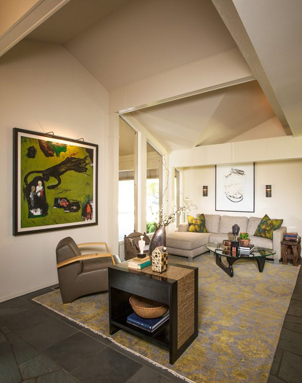 The home's dramatic entryway provides glimpses into the downstairs common areas, including the living room and kitchen.