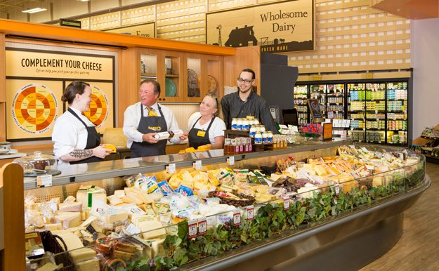 Reasor discusses products with employees at the cheese counter of the Brookside location of Reasor's foods.