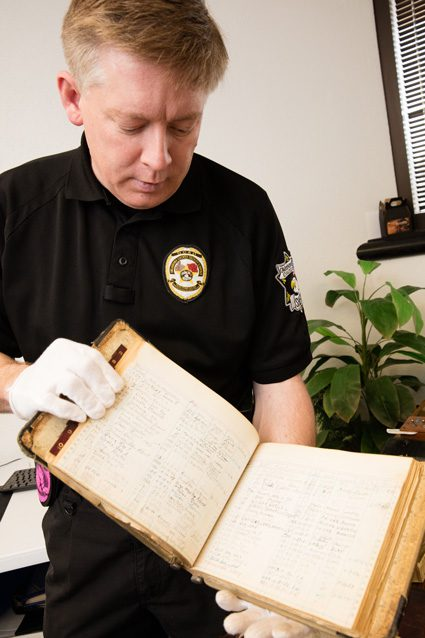 Oklahoma County Sheriff's Deputy Bradley Wynn displays an artifact at the Oklahoma County Jail. Wynn is working to preserve the artifacts through digital technology.  Photo by Brent Fuchs.