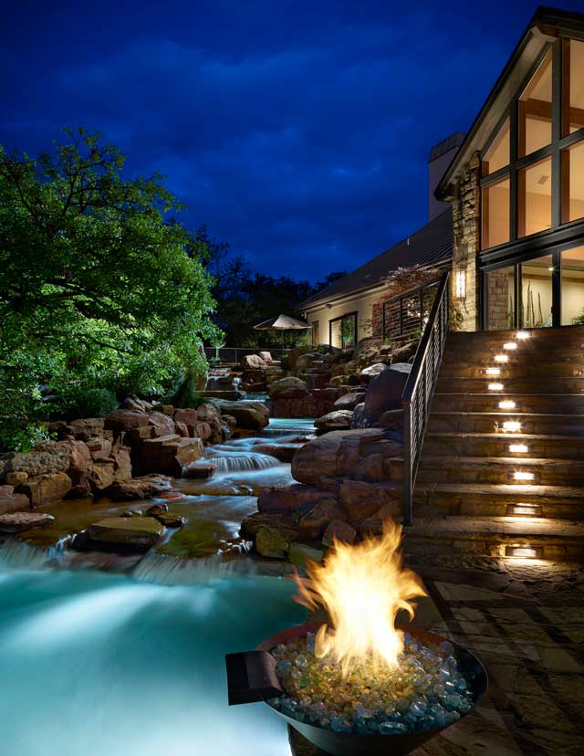 Dramatic lighting illuminates the rear setting of this luxurious home. A natural waterfall cascades over rocks, rushing toward a pool. Flagstone steps lead to the rear patio.