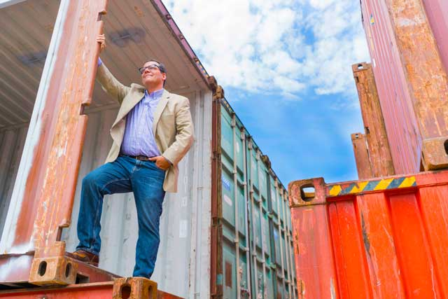 Casey stowe with the shipping containers that will house the stores at The Boxyard.