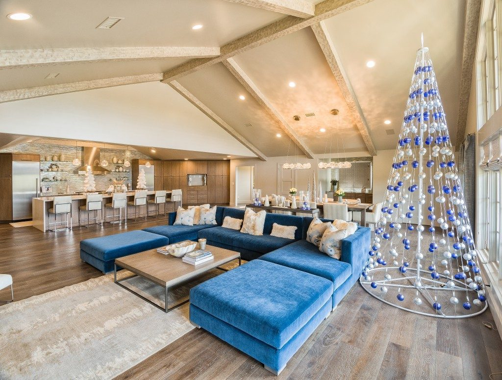A pyramid metal tree dressed with blue and silver ornaments, complements the blue sofa in the spacious living/dining/kitchen great room area. Photos by Scott Johnson, Hawks Photography