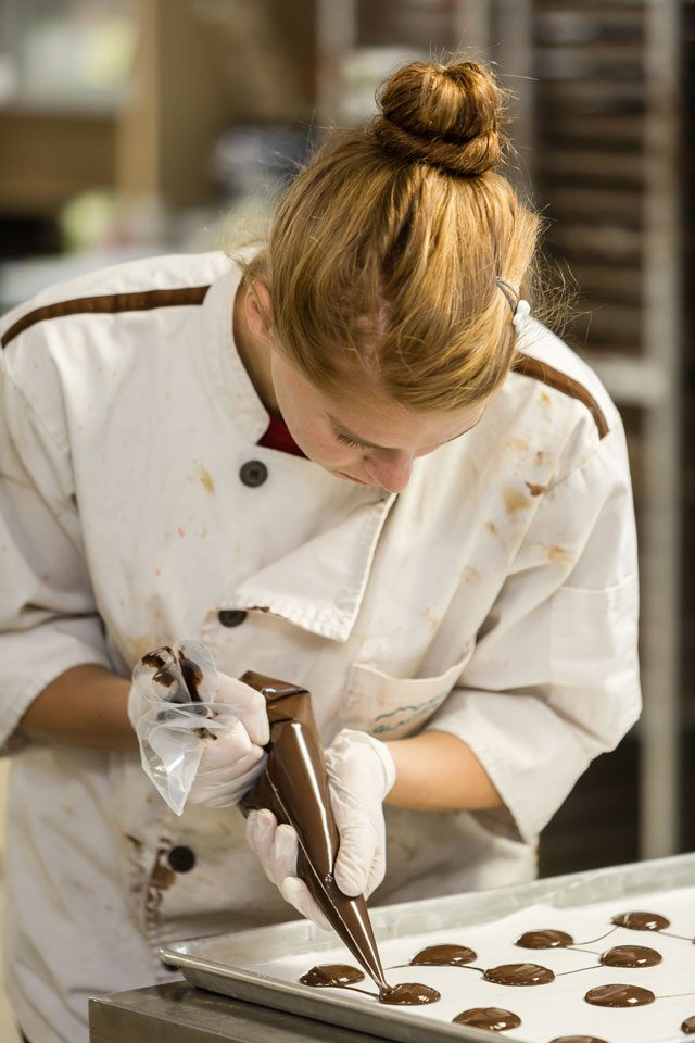 Erin Groff works on creating chocolate in the Glacier factory. Photo by Chris Humphrey Photographer.