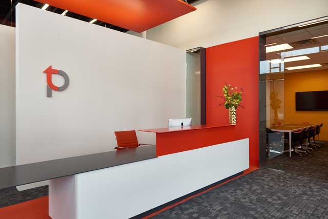 : A crisp, streamlined, modern look greets clients at TPC Studios. Different shades of warm red are among highlights in the color palette.