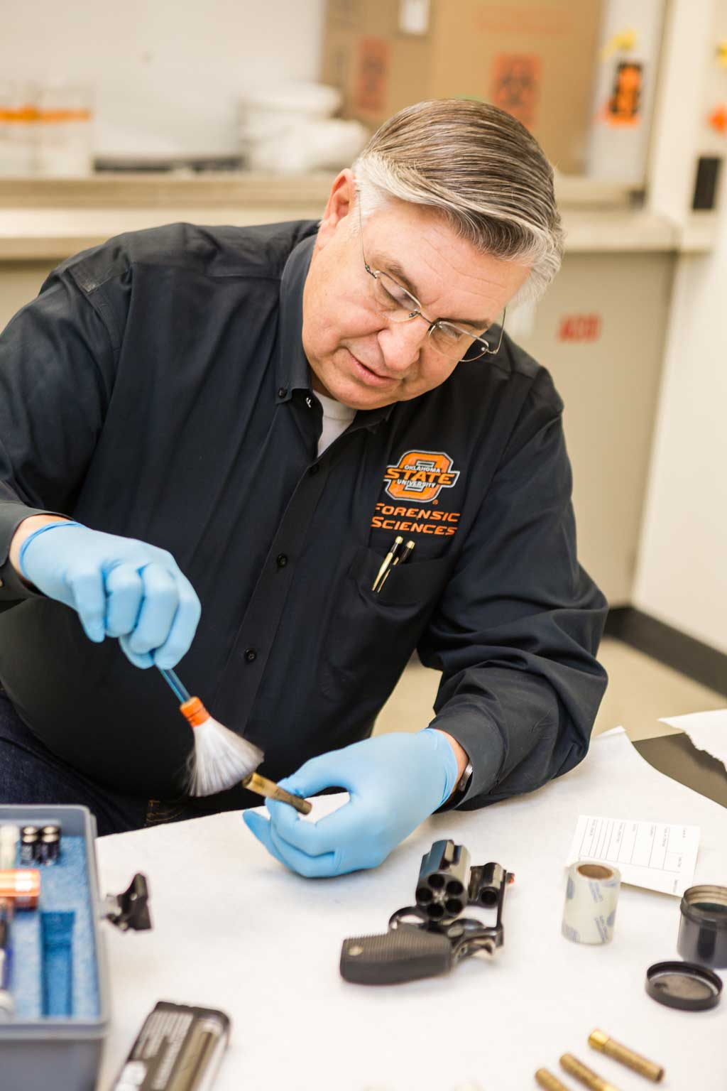 Forensics professor Ton Thrasher has students collect physical and behavioral evidence as they work a crime scene. Photos by Chris Humphrey Photographer.